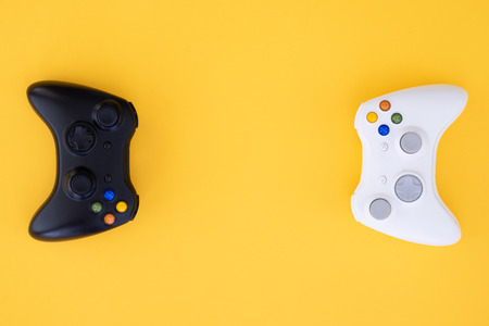 Foto de Black and white joystick on a yellow background. White and black gamepad is isolated on a yellow background. Video game competition. Gaming concept. Top view. Flat lay - Imagen libre de derechos