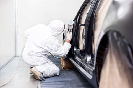 Foto de worker painting a car in a special painting box, wearing a white costume and a breathing helmet as protection gear - Imagen libre de derechos