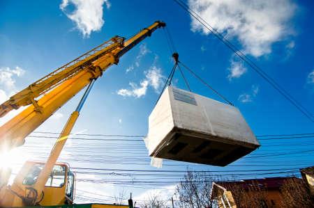 Foto de Industrial Crane operating and lifting an electric generator against sunlight and blue sky - Imagen libre de derechos