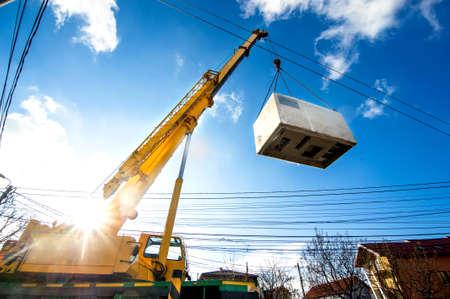 Foto de Mobile crane operating by lifting and moving an heavy electric generator  - Imagen libre de derechos