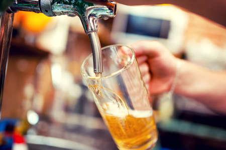 Foto de close-up of barman hand at beer tap pouring a draught lager beer - Imagen libre de derechos