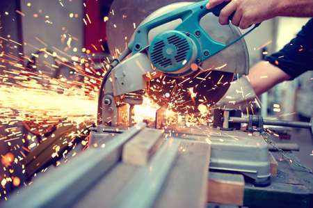 Photo pour industrial engineer working on cutting a metal and steel with compound mitre saw with sharp, circular blade - image libre de droit