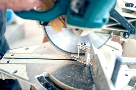 Photo pour worker or handyman cutting PVC profile with circular saw,sliding compound mitre saw. Pvc windows and doors production factory  - image libre de droit