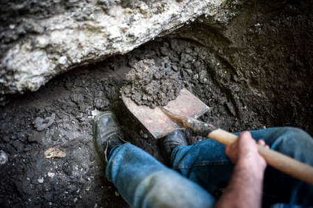Foto de man digging a hole in the ground with shovel and spade - Imagen libre de derechos