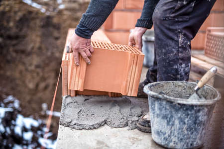 Photo for Construction site of new house, worker building the brick wall with trowel, cement and mortar - Royalty Free Image