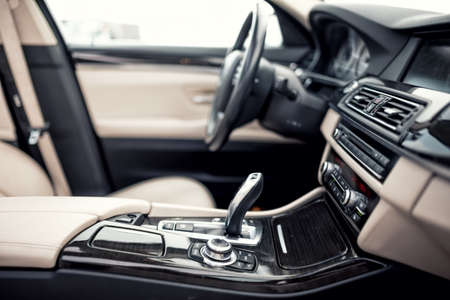 Photo pour Modern beige and black interior of modern car, close-up details of automatic transmission and gear stick against steering wheel background and dashboard - image libre de droit