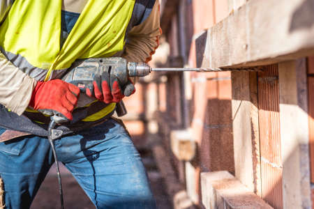 Photo pour Worker using a drilling power tool on construction site and creating holes in bricks - image libre de droit