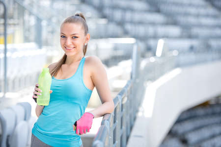 Photo pour Smiling blonde fitness woman drinking water after complete outdoor workout - image libre de droit