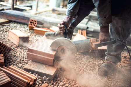 Foto de Industrial construction worker using a professional angle grinder for cutting bricks and building interior walls - Imagen libre de derechos