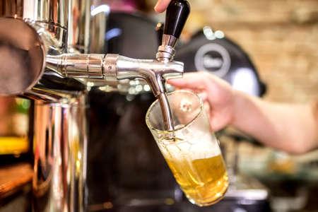 Foto de barman hand at beer tap pouring a draught lager beer serving in a restaurant or pub - Imagen libre de derechos