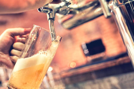 Foto de Hand of bartender pouring a large lager beer in tap - Imagen libre de derechos