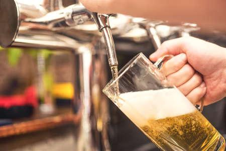 Foto de bistro waiter serving a cold chill beer. Hand of barman pouring a lager beer from tap - Imagen libre de derechos