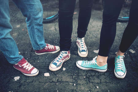 Photo pour Young rebel teenagers wearing casual sneakers, walking on dirty concrete. Canvas shoes and sneakers on female adults - image libre de droit
