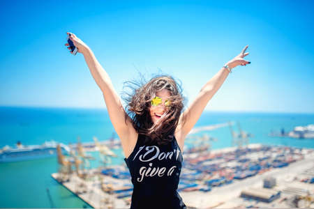 Photo for Attractive girl wearing black tank top smiling, laughing and taking pictures with camera phone. Traveling concept with happy woman. - Royalty Free Image
