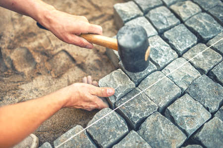 Photo pour Close-up of construction worker installing and laying pavement stones on terrace, road or sidewalk. Worker using stones and rubber hammer to build stone sidewalk - image libre de droit
