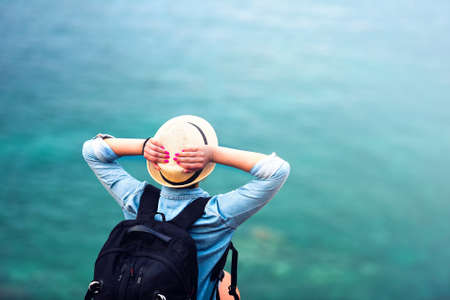 Photo for young woman on summer vacation, hiking on coastline and staring at sea wearing hat and backpack. Travel and adventure concept - Royalty Free Image