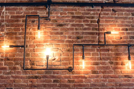 Photo pour interior design of vintage wall. Rustic design, brick wall with light bulbs and pipes, low lit bar interior - image libre de droit