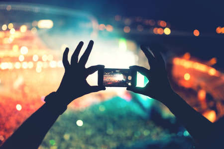 Foto de Silhouette of hands using camera phone to take pictures and videos at pop concert, festival. Soft effect on photo - Imagen libre de derechos