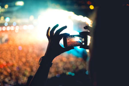 Photo for Silhouette of a man using smartphone to take a video at a concert. Modern lifestyle with hipster taking pictures and videos at local concert. Main focus on camera and lights. - Royalty Free Image