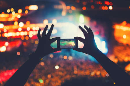 Photo for young hipster taking photos and videos at concert. Modern lifestyle with smartphone and parties. - Royalty Free Image