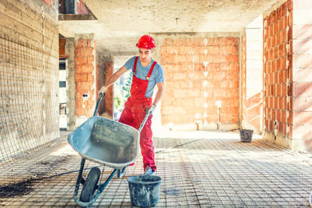 Photo pour worker with empty wheelbarrow on construction site - image libre de droit