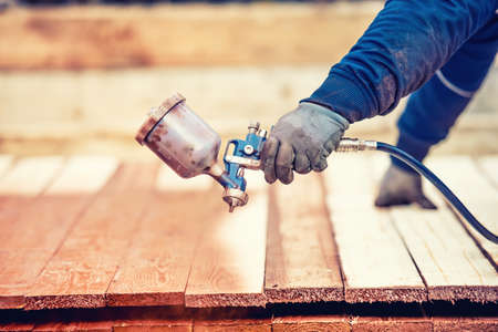 Foto de Man using protective gloves painting wooden timber with spray paint gun - Imagen libre de derechos
