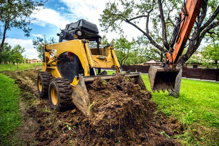 Photo for Yellow mini bulldozer working with earth, moving soil and doing landscaping works - Royalty Free Image