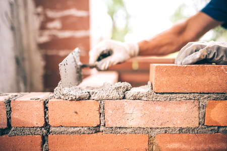 Photo for Bricklayer worker installing brick masonry on exterior wall with trowel putty knife - Royalty Free Image