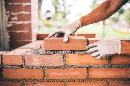 Foto de professional construction worker laying bricks and building barbecue in industrial site. Detail of hand adjusting bricks - Imagen libre de derechos
