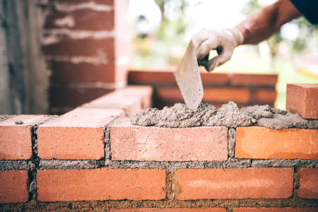 Foto de industrial Construction bricklayer worker building walls with bricks, mortar and putty knife - Imagen libre de derechos