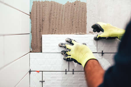 Foto de industrial construction worker installing small ceramic tiles on bathroom walls and applying mortar with trowel - Imagen libre de derechos