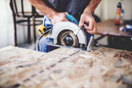 Photo pour Carpenter using circular saw for cutting wooden boards. Construction details of male worker or handy man with power tools - image libre de droit