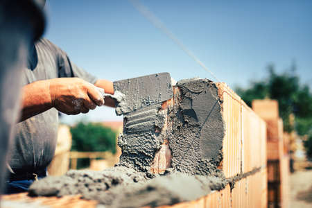 Foto de Bricklayer construction worker installing brick masonry on exterior wall with trowel putty knife - Imagen libre de derechos