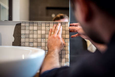 Photo for Industrial worker applying mosaic tiles in bathroom walls - Royalty Free Image