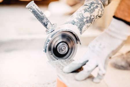 Foto de close up of industrial tool, grinder cutting piece of stone. Marble cutting at construction site - Imagen libre de derechos