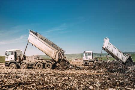 Foto de Industrial heavy duty dumper trucks unloading at construction site - Imagen libre de derechos