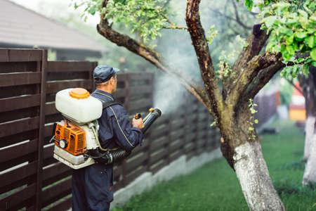 Photo pour agricultural details - farmer working, spraying pesticides in fruit orchard - image libre de droit