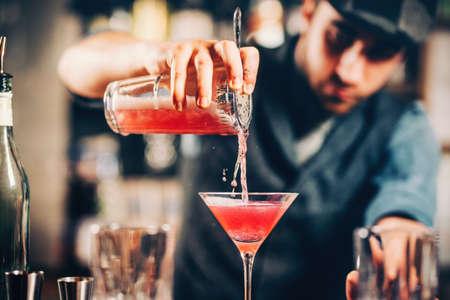 Foto de barman preparing and pouring red cocktail in martini class. cosmopolitan cocktail with bar background - Imagen libre de derechos