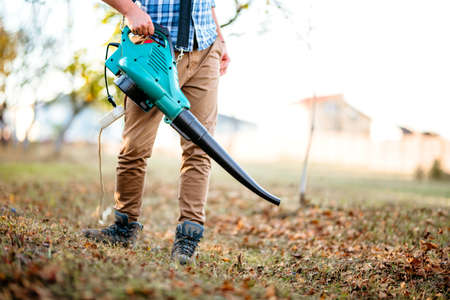 Foto de Gardener clearing up leaves using an electric leaf blower tool. Gardening details - Imagen libre de derechos