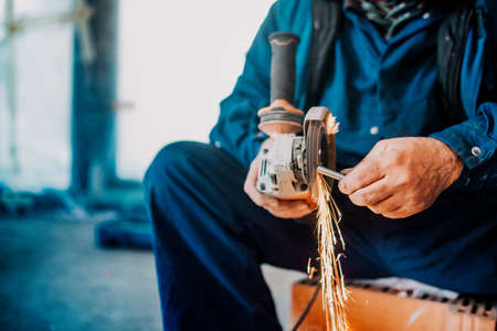Foto de Factory worker cutting iron and metal using grinder and generating sparks on construction site - Imagen libre de derechos