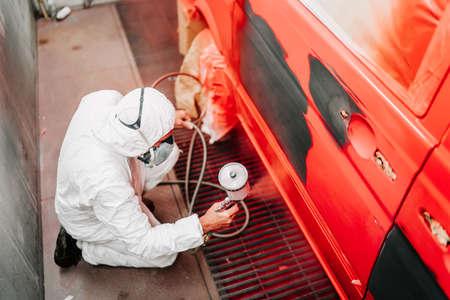 Foto de Auto mechanic painter painting a red car, a van in special booth. automotive industry details - Imagen libre de derechos