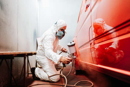 Foto de mechanic male worker painting a car in a special painting box, wearing a white costume and protection gear - Imagen libre de derechos