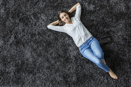 Foto de Young woman laying on the carpet - Imagen libre de derechos