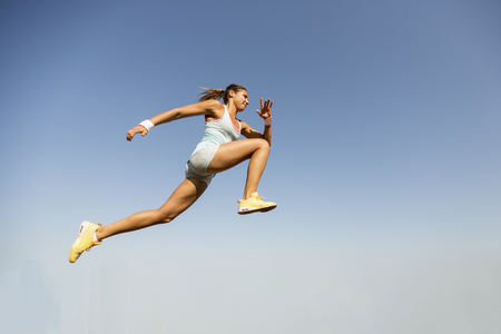 Photo pour Young woman taking long jump - image libre de droit