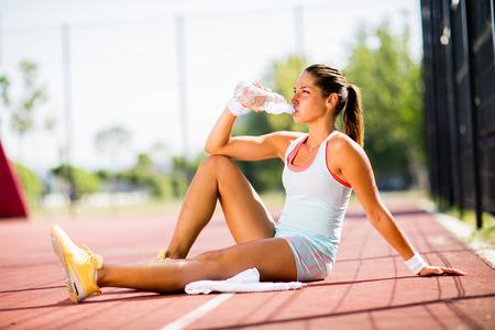 Foto de Sporty young woman drinking water - Imagen libre de derechos