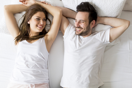 Photo for Young loving couple in the bed - Royalty Free Image