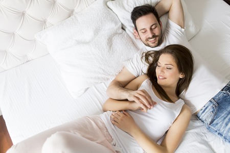Foto de Young loving couple in the bed - Imagen libre de derechos