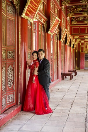 Foto de HUE, VIETNAM - FEBRUARY 19, 2017: Unidentified wedding couple at Royal Palace in Hue, Vietnam. Traditional Vietnamese wedding is one of the most important ceremonies in Vietnamese culture - Imagen libre de derechos