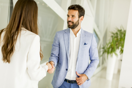Photo for View at smiling young businessman making handshake with a businesswoman - Royalty Free Image