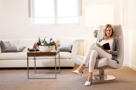Foto für View at young woman reading a book and sitting on comfortable chair at home - Lizenzfreies Bild